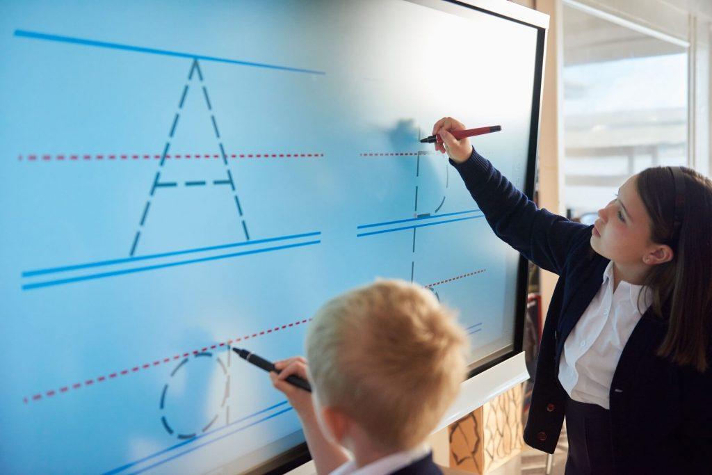 deux eleves utilisent l ecran interactif en simultane